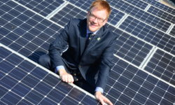 Warren Whyte with solar panel array on the roof of County Hall